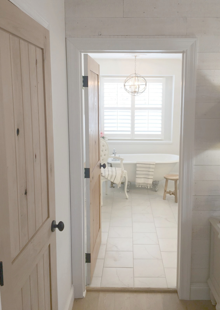 White French country master bathroom with rustic alder door, calacatta-look porcelain tile and clawfoot tub. #hellolovelystudio #bathroomdesign #bathroomdecor #frenchcountry #clawfoottub #alderdoor