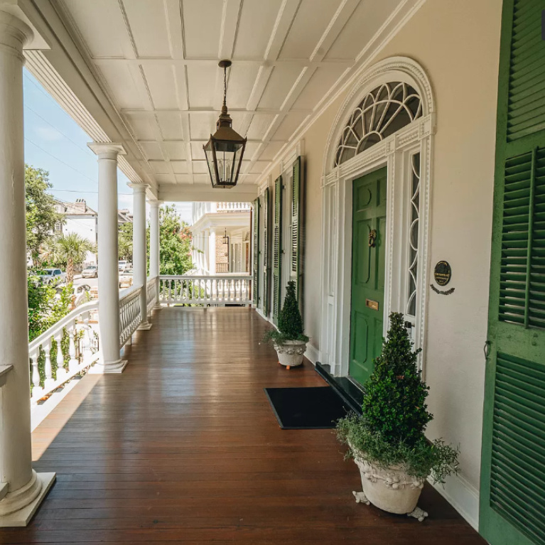 Classic and timeless piazza on Battery Street in Charleston with green shutters and beautifully stained wood floor. Peek at Charming Porch Inspiration & Decor Ideas for your home! #piazza #charlestonhouse #frontporch #greenshutters #historichome #houseexterior #southernhomes
