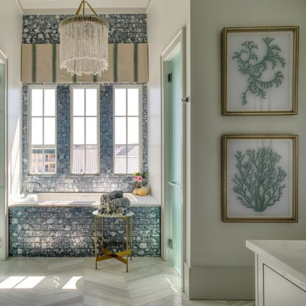 Stone tile floor to ceiling in a luxurious blue and white coastal bath with architecture by Geoff Chick.