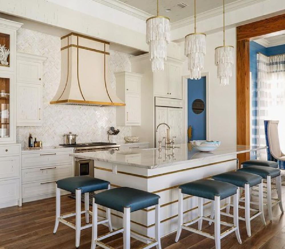 Lacquer pecky cypress cabinets, custom hood and mosaic backsplash in a chic coastal kitchen in Watercolor with architecture by Geoff Chick.