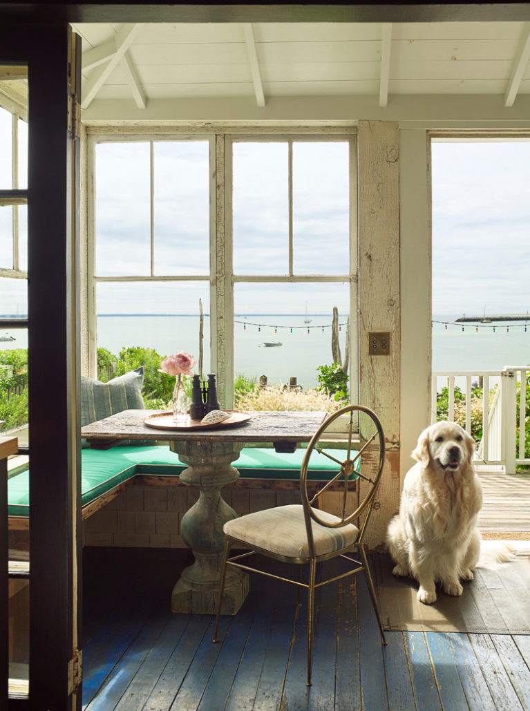 Ken Fulk's charming seaside cottage porch in Provincetown - photo by Tria Giovan for Jennifer Rudick's SUMMER TO SUMMER. #cottagestyle #seasidecottage #porch #newengland #interiordesign #kenfulk #goldenretriever #englishcream