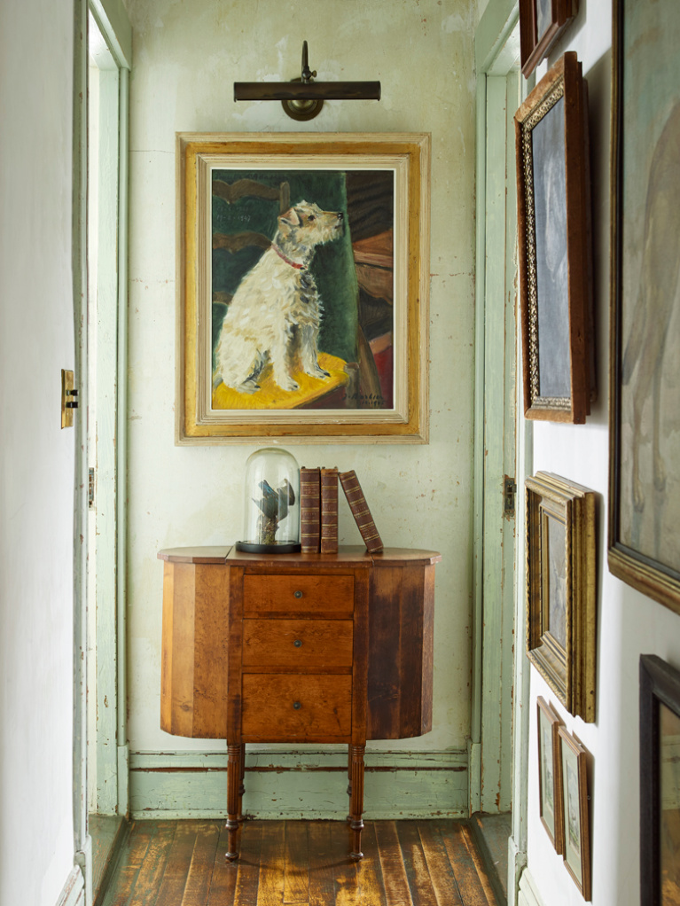 Collection of dog portraits in the hallway of a Provincetown seaside summer home with interiors by Ken Fulk. Photo by Tria Giovan for Jennifer Ash Rudick's Summer to Summer. #dogpaintings #interiordesign #dogportrait #kenfulk #vintagestyle #traditionaldecor