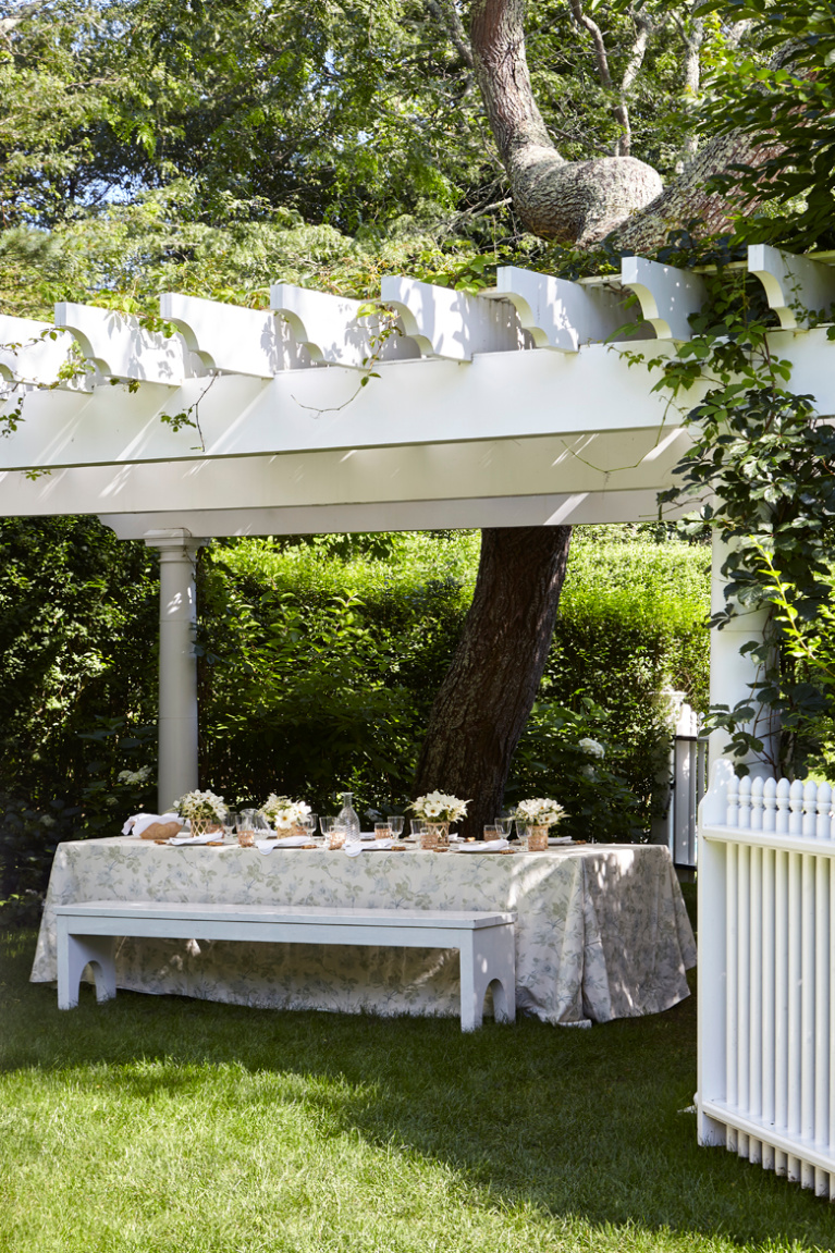 White pergola over a skirted picnic table set for lunch in the East Hampton garden of Aerin Lauder. Photo by Tria Giovan for Summer to Summer (Rudick). #aerinlauder #hamptonshome #summerhome #pergolas #tablescape #outdoordining #coastalstyle