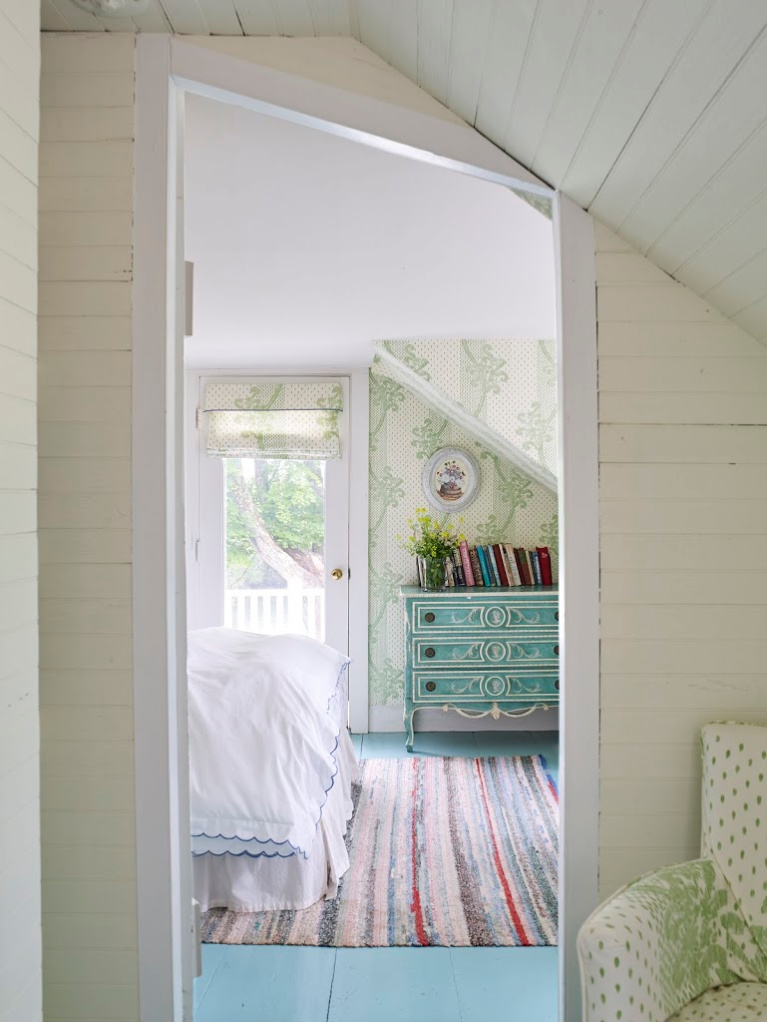 In a seaside cottage bedroom in Maine, a beautiful wallpaper (Kinnicutt by Sister Parish Design) graces the walls while turquoise paint enlivens the wood floors. #bedroomdesign #coastalstyle #vintagestyle #sisterparish #interiordesign #kinnicutt #wallpaper