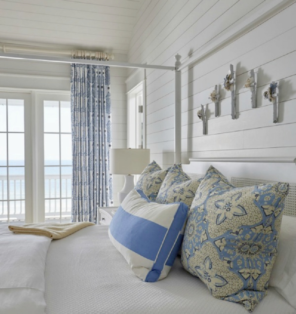 Luxurious and lovely coastal bedroom with blue tripe pillow, shiplap walls, and architecture by Geoff Chick.