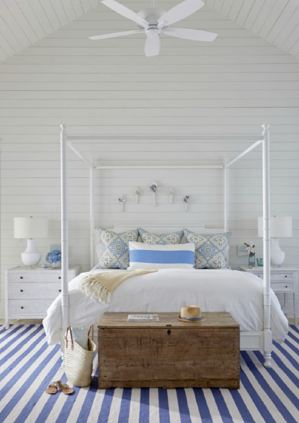 White coastal style bedroom with blue stripe rug, poster bed, and shiplap walls - architecture by Geoff Chick.