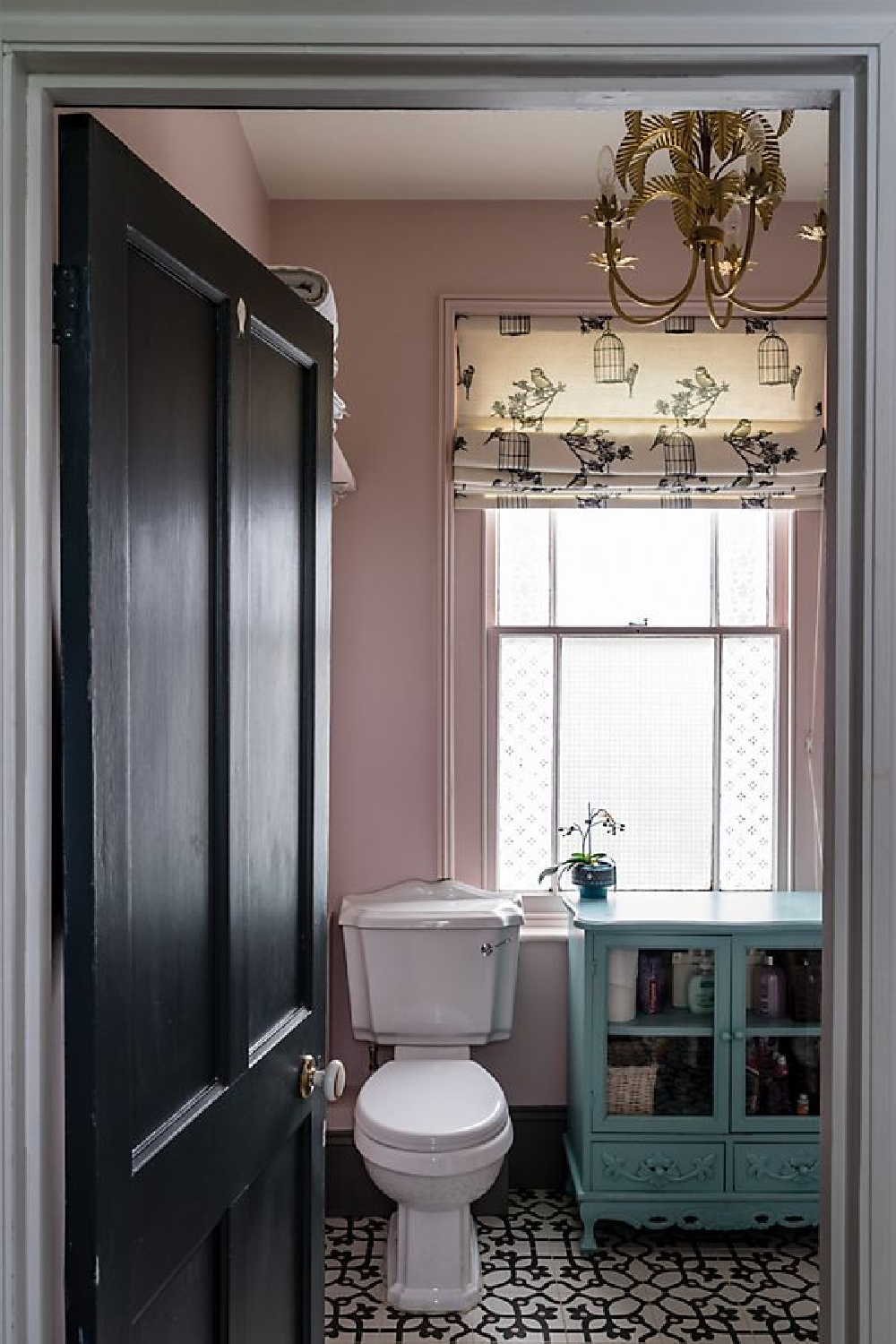 Calamine No.230 Farrow & Ball in a bathroom with freestanding teal cupboard with glass doors.
