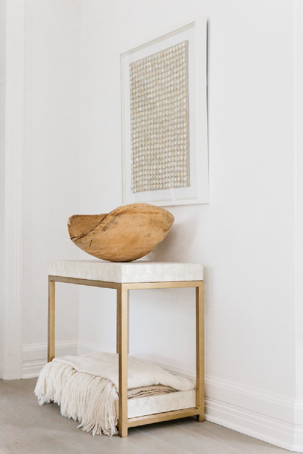 Mother of Pearl framed art over a marble and brass accent table topped with rustic wood dough bowl in Erin Fetherston's white on white living room in LA.