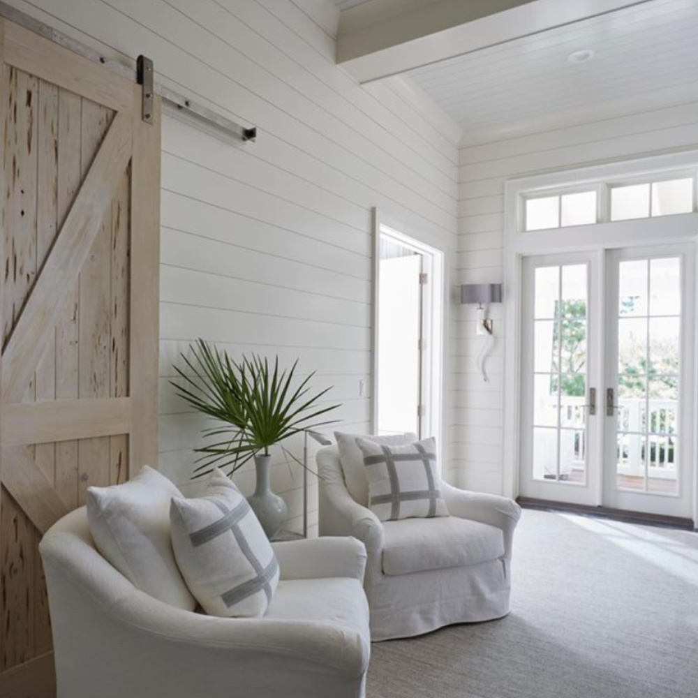 Classic coastal interior with white shiplap, rustic barn door and French doors - architecture by Geoff Chick.