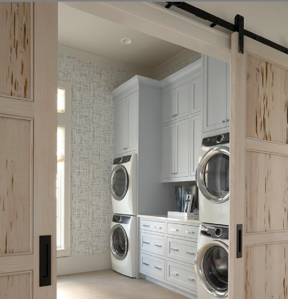Pickled pecky cypress barn doors grace a laundry room with coastal style and light blue cabinets - architecture: Geoff Chick. #laundryrooms