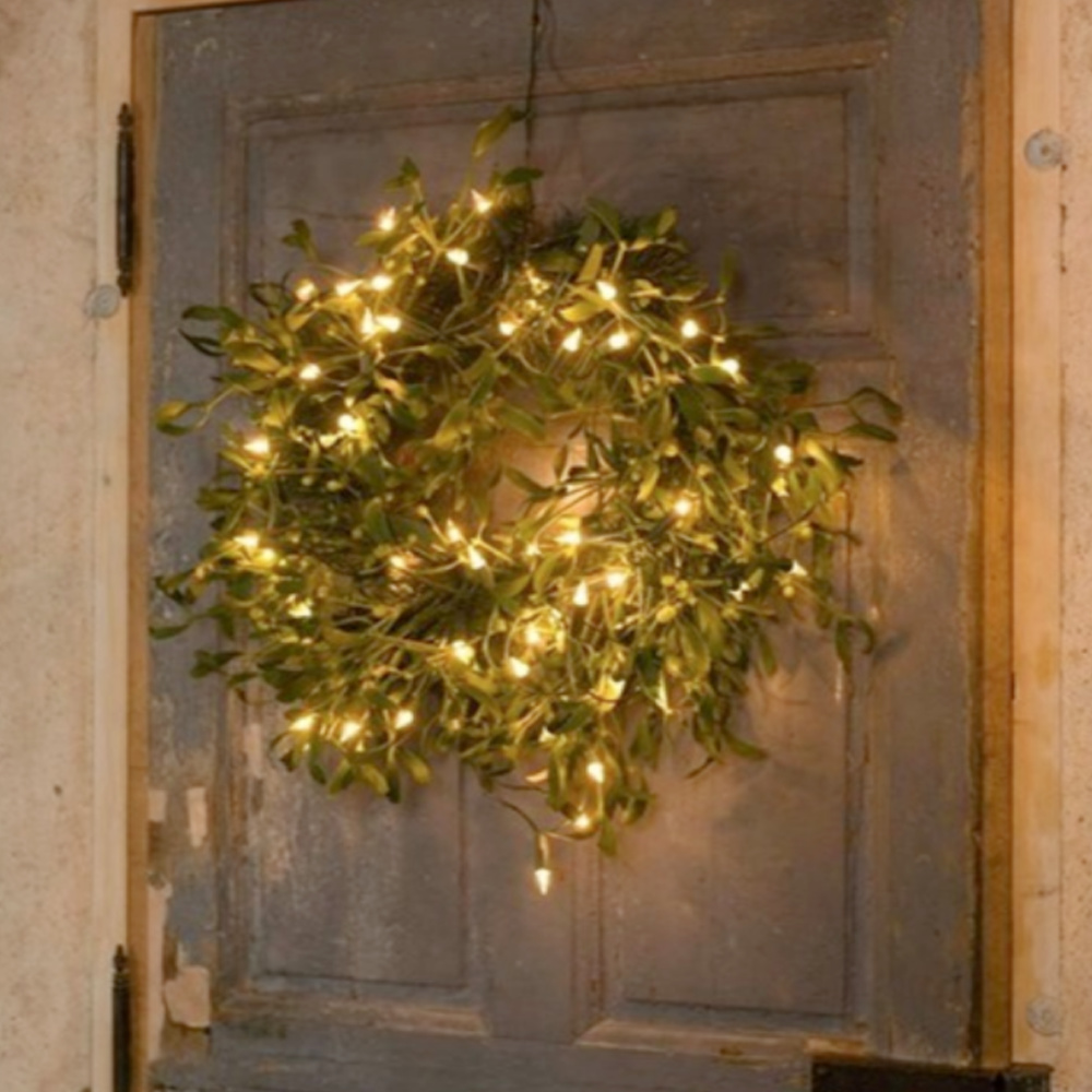 Holiday mistletoe wreath with white lights on a rustic weathered door in France - @loirevalleycooking. #frenchcountrychristmas #christmaswreaths