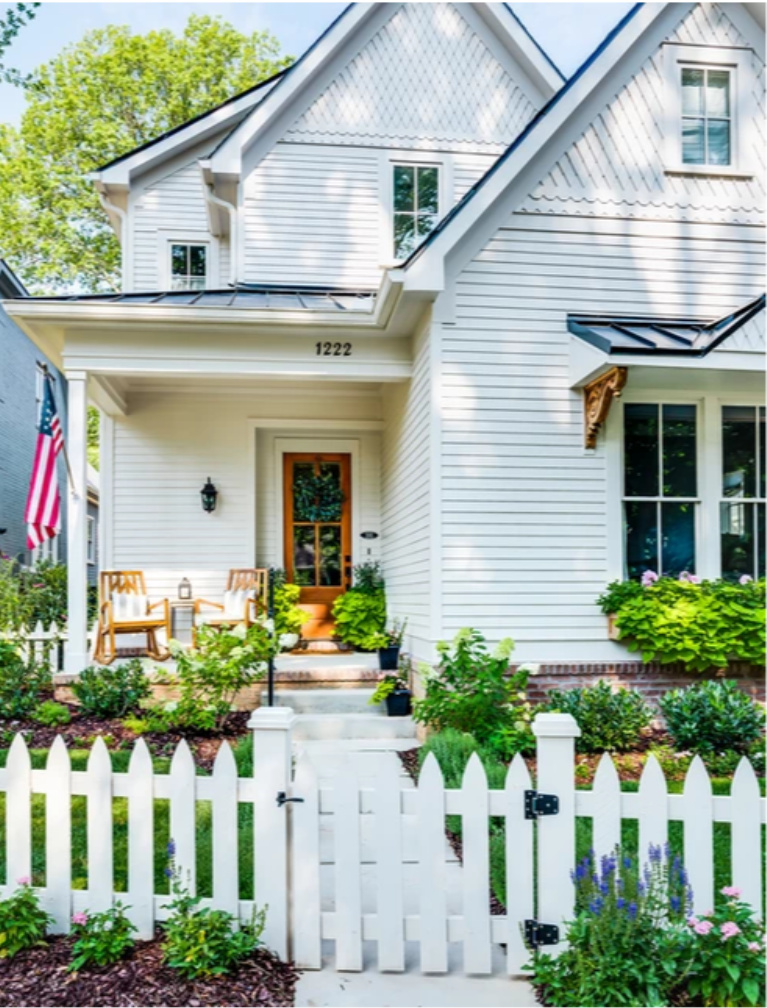 Darling Victorian home with front porch, picket fence, and American flag - Garden Gate Homes.  Come peek at Charming Porch Inspiration & Decor Ideas. #homeexteriors #housedesign #victorianhomes #frontporch #curbappeal