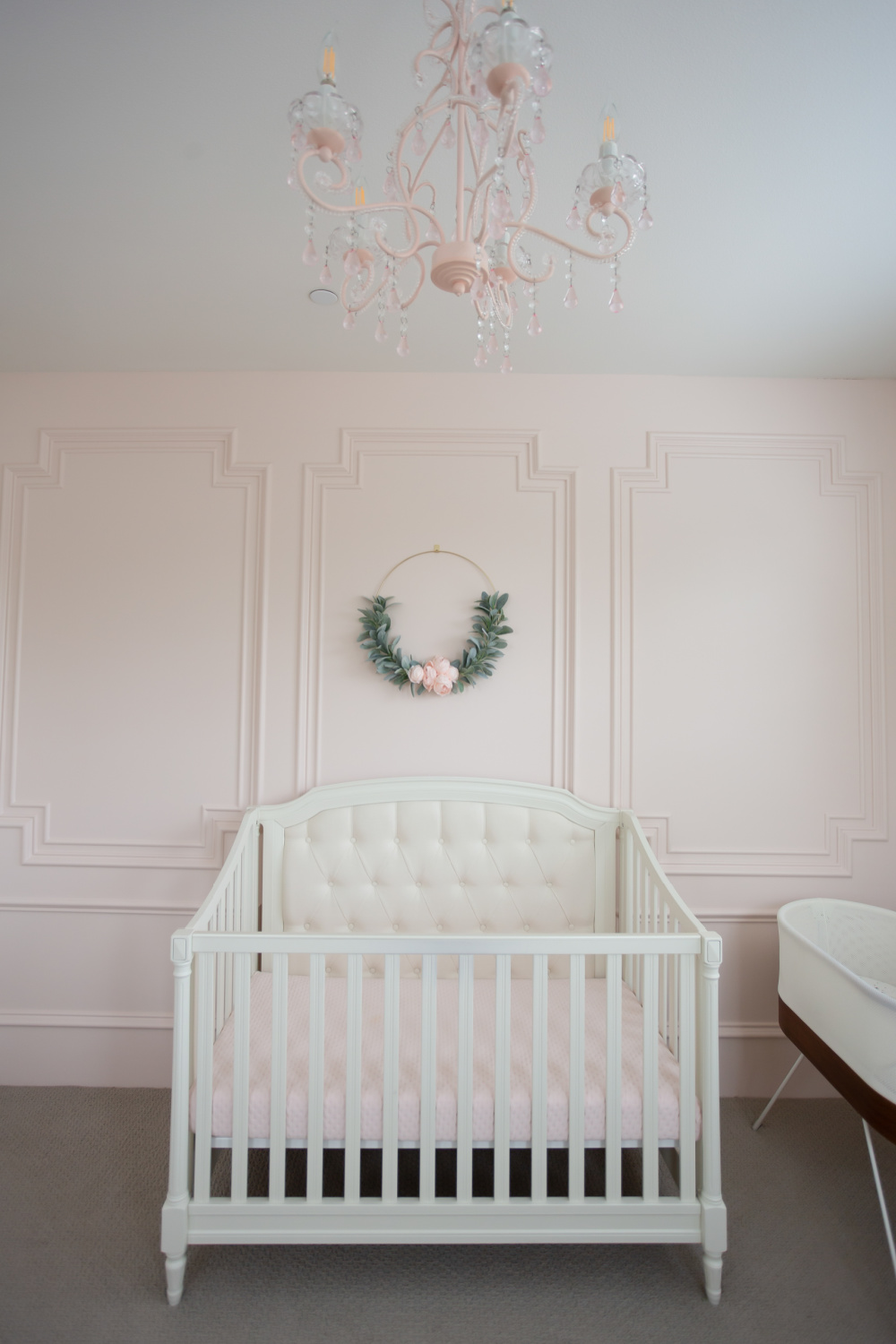 Intimate White (BM) pale blush pink painted accent wall with millwork in a beautiful nursery - StylishPetite. #intimatewhite #blushpink