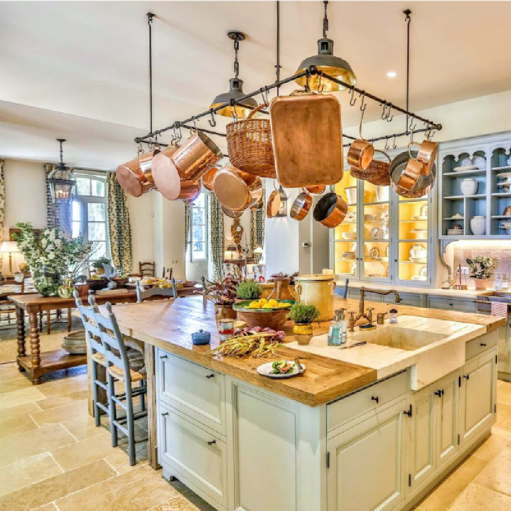 French farmhouse kitchen with copper pans on rack, light blue cabinetry, and stone floors - Le Mas des Poiriers.