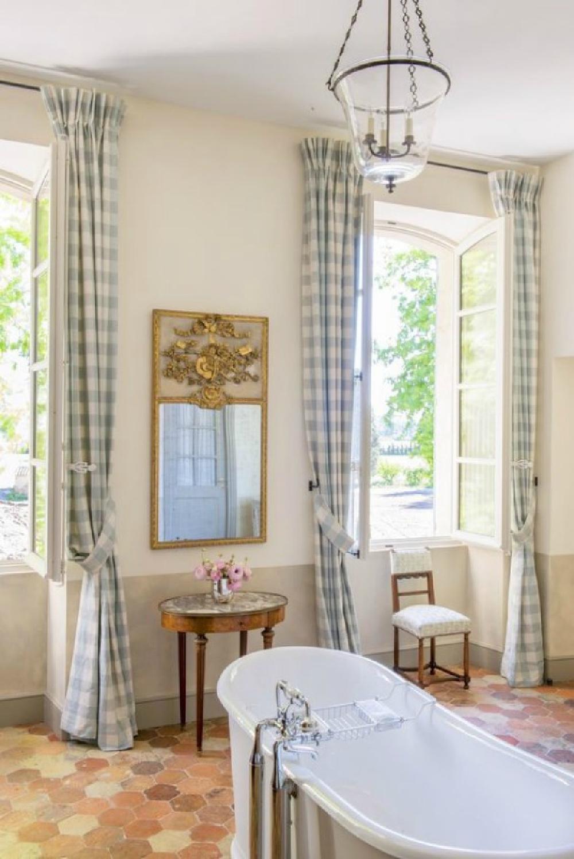 Blue check curtains, terracotta hex tiles, and clawfoot tub in a Provence farmhouse (Le Mas des Poiriers).