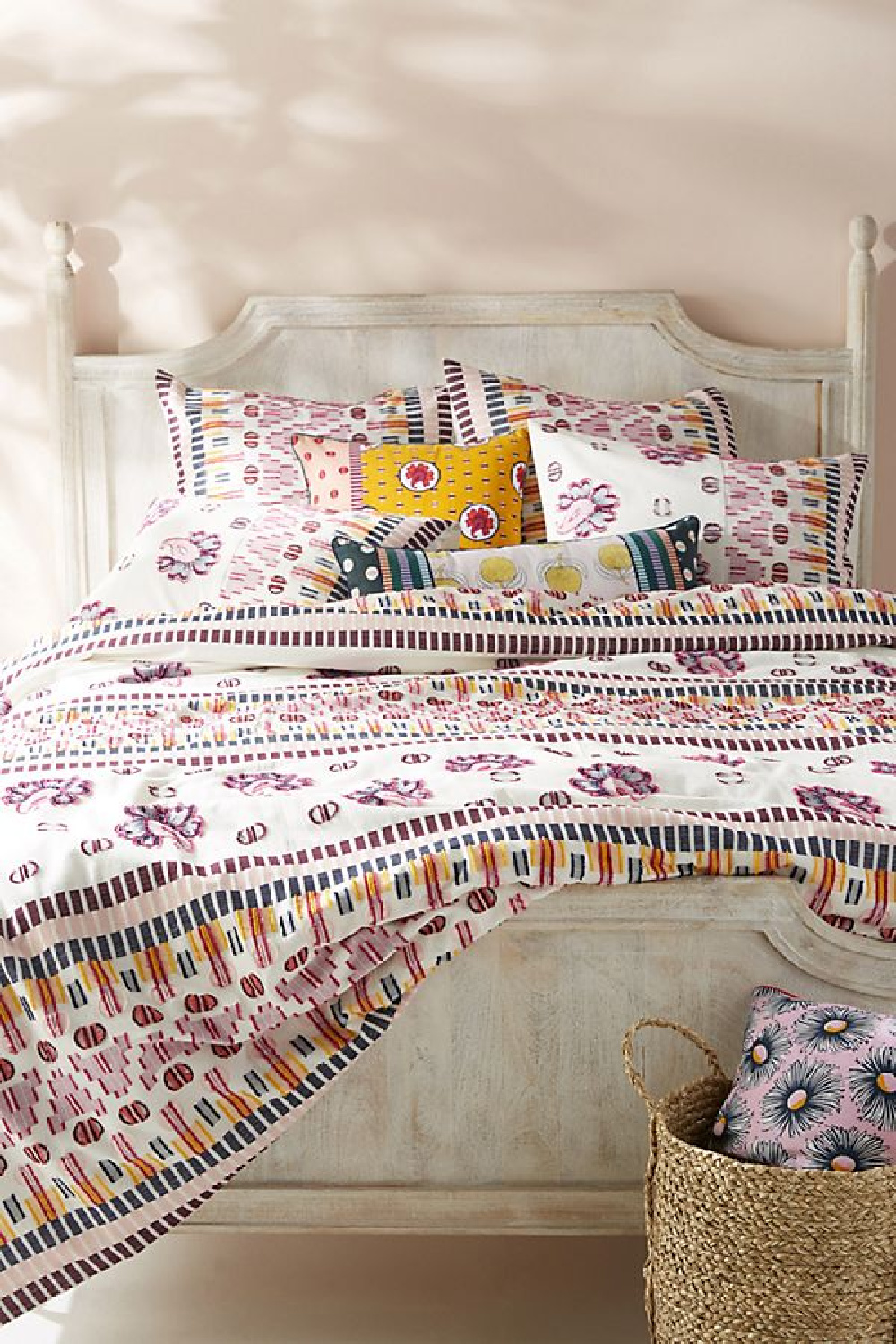 Pink Ground No.202 - Farrow & Ball paint in a bedroom with colorful print bedspread and distressed panel bed.