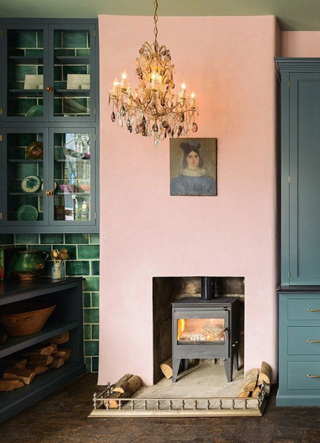 Pink plaster walls surround a woodstove in an English country kitchen by deVOL with green cabinets and tile. Not sure how to work blush into your home? See this story on Hello Lovely Studio!