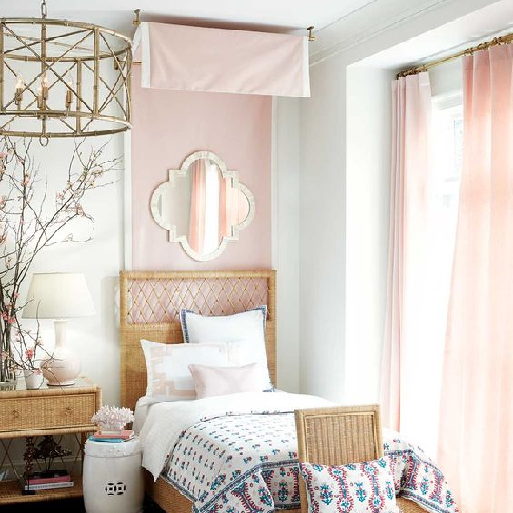 Blush pink bedroom with wicker bed designed by Suzanne Kasler for Ballard Designs.