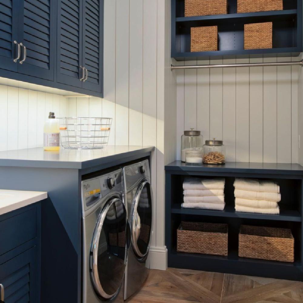 Coastal laundry room with navy blue plantation style cabinets, shiplap, and smart storage - StudioMInteriors. #dreamlaundryroom #navyblue