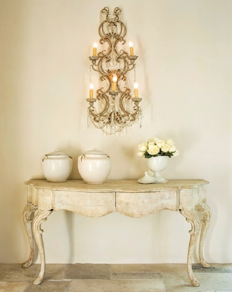 Sophisticated French inspired vignette with French pots and fanciful wall sconce in a Houston home with interiors designed by Pamela Pierce. #whitedecor #PamelaPierce #FrenchCountry #biot