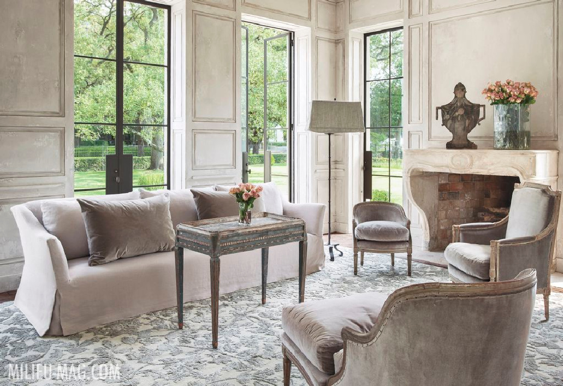 Luxurious and elegant French living room designed by Pamela Pierce with antique stone fireplace mantel and soothing serene neutrals. #interiordesign #frenchcountry #elegantdecor #pamelapierce #livingrooms
