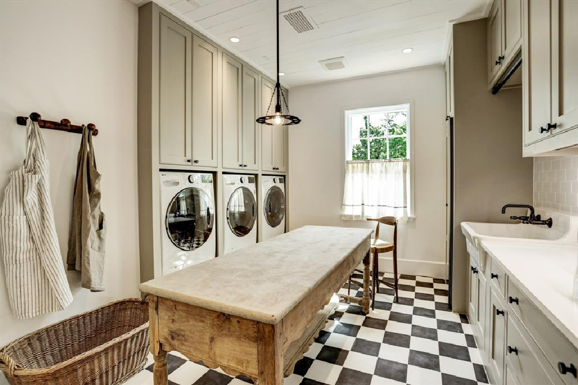 Laundry room with antique table and checker flooring in MILIEU Showhouse 2020 - featuring exceptional designers including Darryl Carter, Kathryn Ireland, Pamela Pierce, Shannon Bowers, and more. #milieushowhouse #interiordesign #designershowhouse #luxuryhome #edwinlutyens #houstonhome #laundryrooms