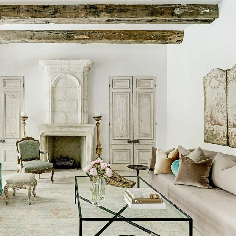 Stunning and sophisticated family room in a French inspired home with 18th century limestone fireplace and rustic ceiling beams. #frenchcountry #interiordesign #luxuryhome #antiques #europeancountry