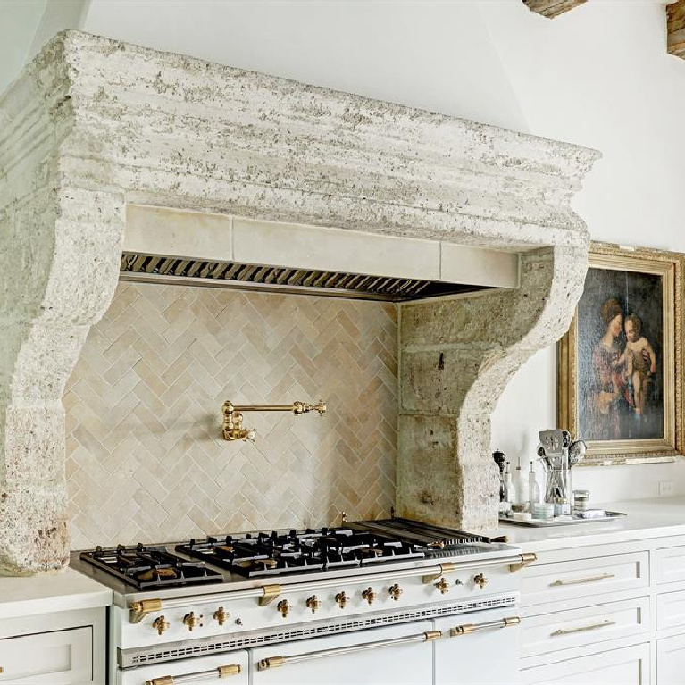 16th century stone mantel above Lacanche range in stunning Houston kitchen with Segreto stone countertop. #frenchkitchens #frenchmantel #oldworldstyle #frenchcountry #chateaudomingue #bespokekitchen #timelessdesign