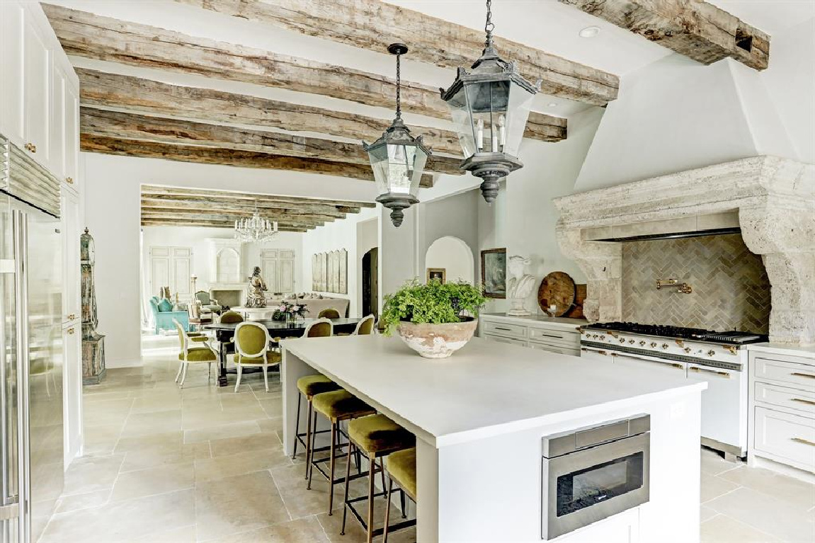 Rustic wood beams and antique street lights from Barcelona in Pale and serene French interiors in a luxurious Houston home built with authentic European materials and bespoke finishes. #timelessdesign #interiordesign #frenchcountry #europeancountry #antiques #oldworldstyle #modernfrench #frenchkitchen