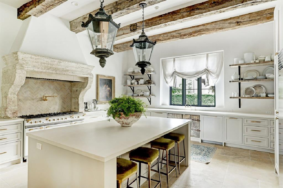 Kitchen with 16th century French mantel in Pale and serene French interiors in a luxurious Houston home built with authentic European materials and bespoke finishes. #timelessdesign #interiordesign #frenchcountry #europeancountry #antiques #oldworldstyle #modernfrench #plasterwalls