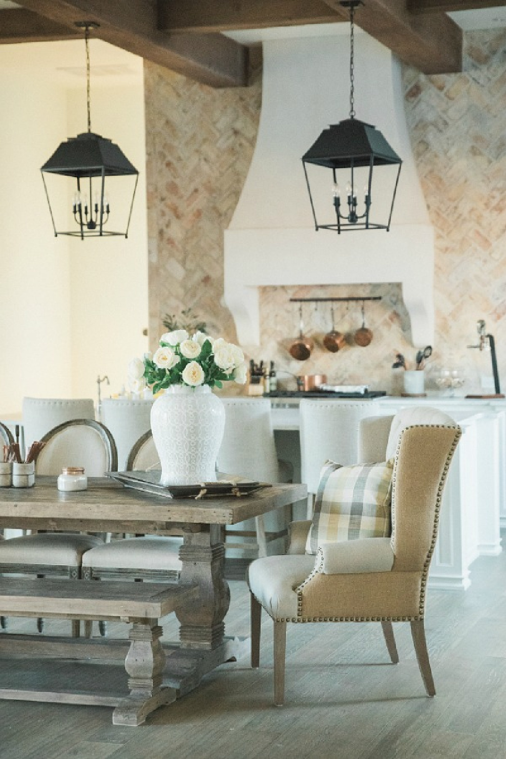 French country farmhouse kitchen with rustic lanterns, farm table, wing chairs, reclaimed Chicago brick, and Sherwin Williams Alabaster white paint on walls. Brit Jones Design. See more Gorgeous European Country Interior Design Inspiration on Hello Lovely. #europeancountry #frenchfarmhouse #interiordesign