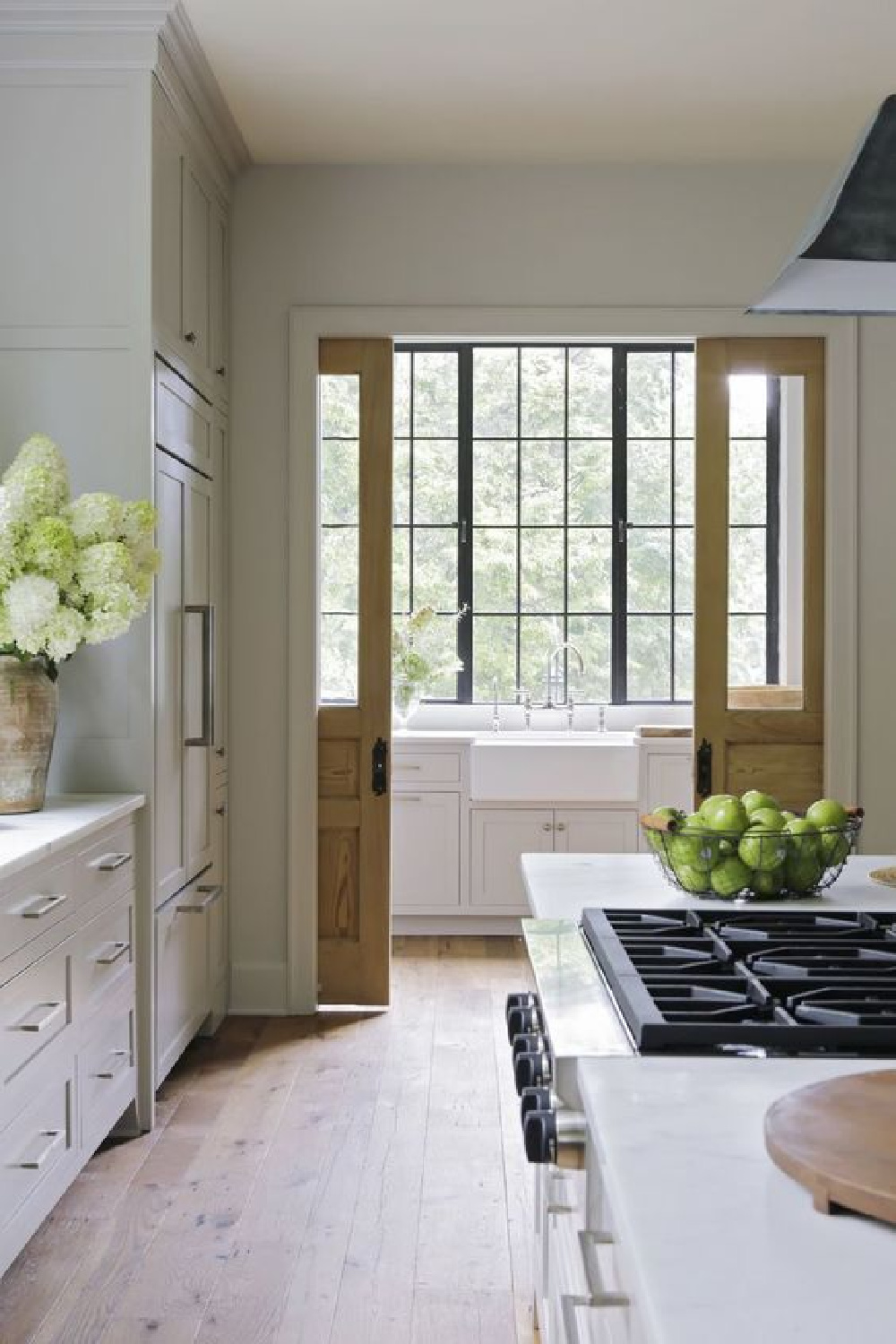 Breathtaking classic country kitchen with farm sink, wood tone pocket doors, steel windows, and putty cabinets - Rachel Halvorson. #countrykitchens #pocketdoors #kitchenarchitecture