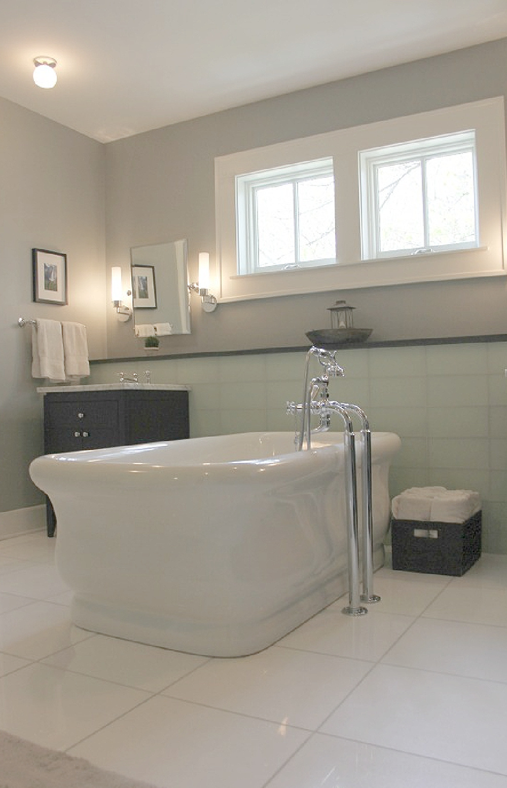 Benjamin Moore Platinum Gray wall color in bath with Waterworks tub, glass tile, and black vanities. #platinumgray #paintcolors