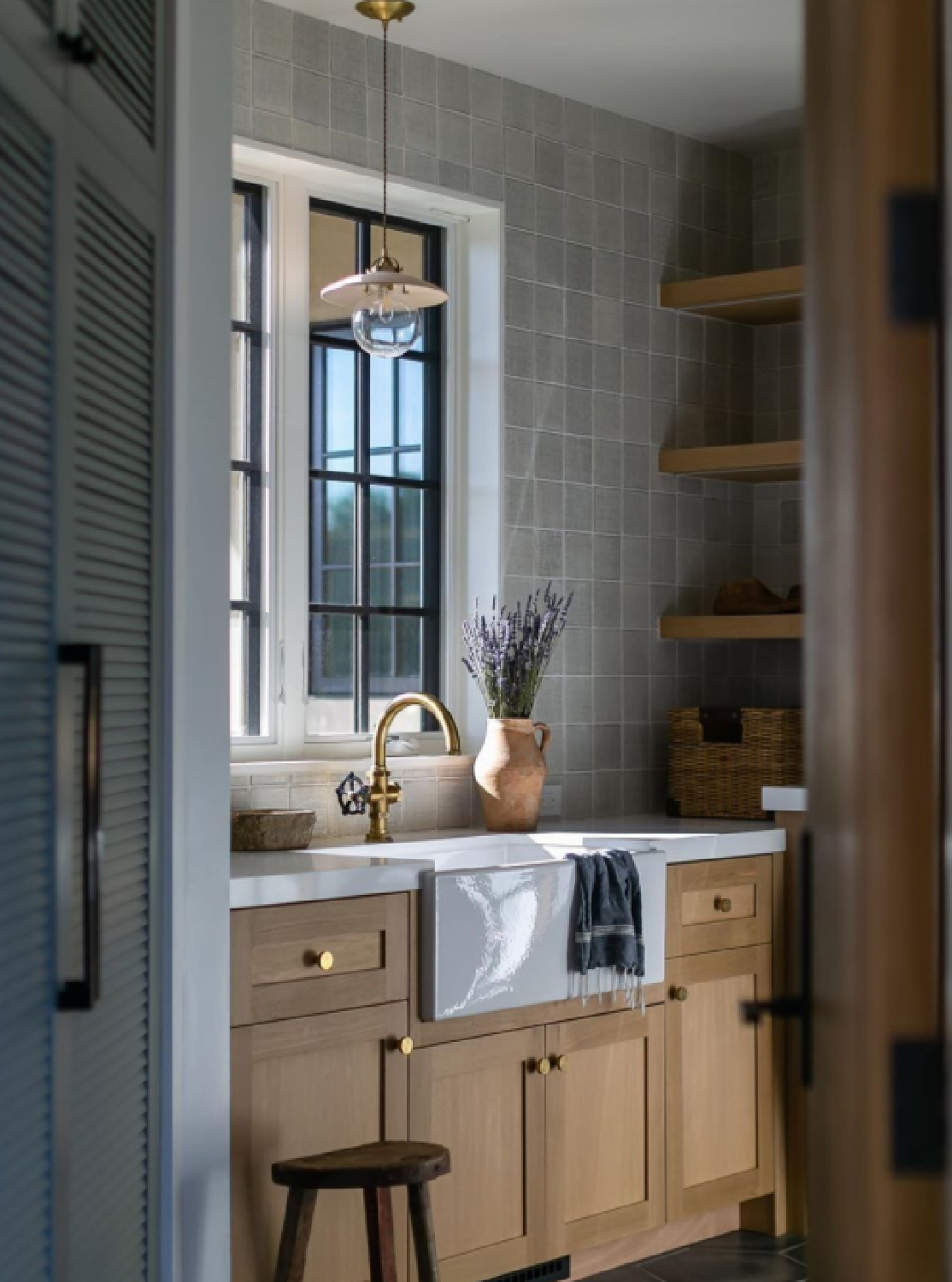 Beautiful classic laundry room with farm sink, windows, wood cabinets, open shelves, and brass hardware - @blackbanddesign #laundryroomdesign