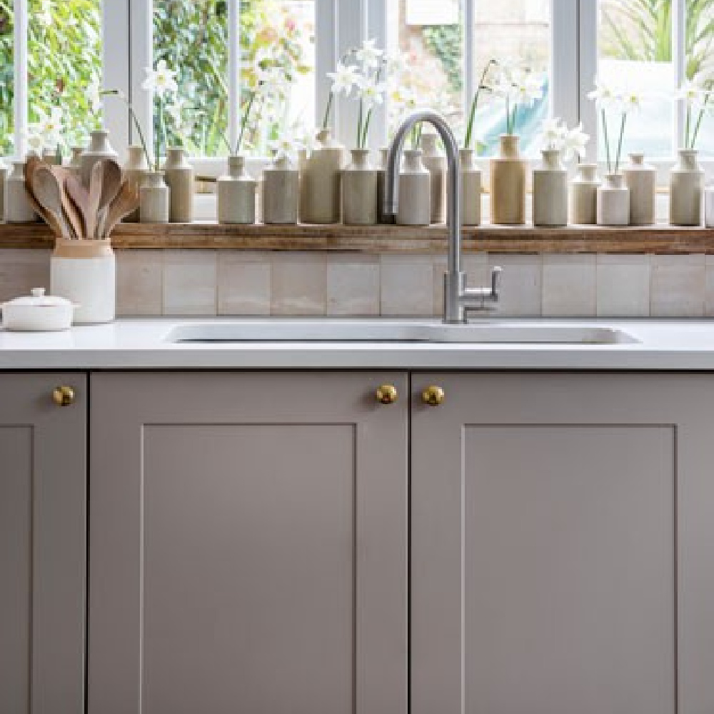 Zellige tile backsplash in a gray English country kitchen with a collection of stoneware bottles - ImperfectInteriors. #zellige #englishcountry #kitchendecor