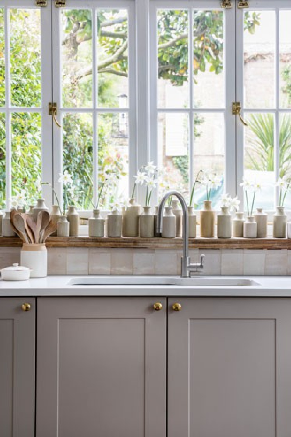 Modern farmhouse classic kitchen with grey cabinets, zellige tile backsplash, and a collection of putty colored stone English pottery lined up on the window sill. Interior Design by Imperfect Interiors. Photo: Chris Snook. #kitchendesign #modernfarmhouse #englishpottery #vintagestyle #slowliving #greycabinets