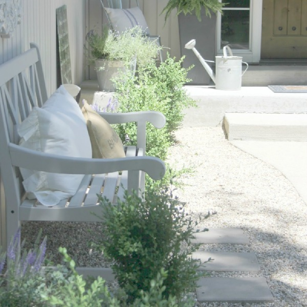 French country courtyard with stone walls, pea gravel, boxwood, lavender, wood furniture, and vintage touches. Come see the before and after of our project on Hello Lovely Studio. #hellolovelystudio #frenchcountry #courtyard #gardeninspiration #renovation