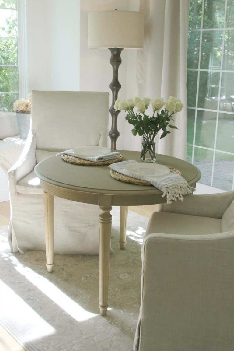Belgian linen slope arm dining chairs and small round breakfast table in serene kitchen - Hello Lovely Studio. #frenchcountry #nordicfrench #belgianlinen #breakfastnook #slopearmchairs #serenedecor