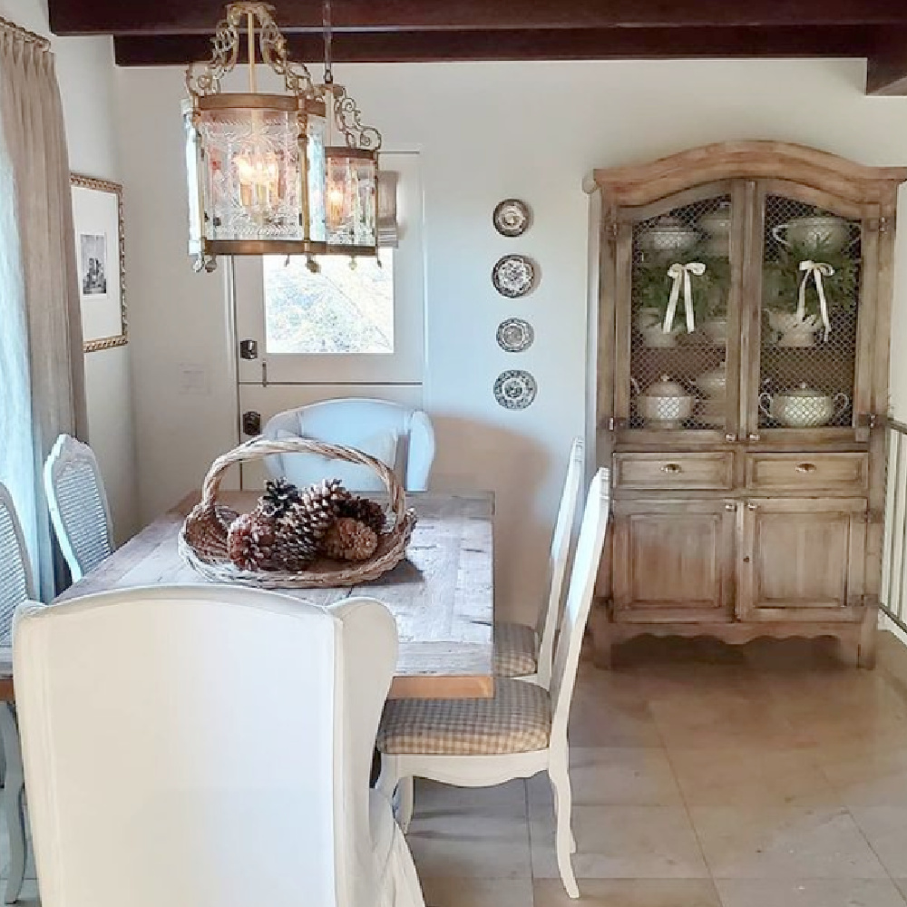 Rustic elegant French farmhouse dining room with lanterns, pale tones, plates on wall and farm table - @thefrenchnestcointeriordesign. #frenchfarmhouse #diningroom