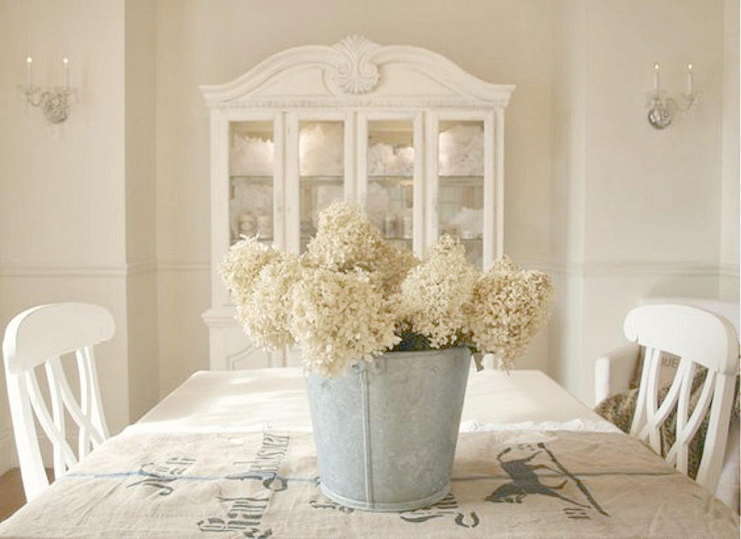 White French Nordic dining room with German antique grainsack and galvanized bucket of hydrangea on table - Hello Lovely Studio. #frenchnordic #diningroom #frenchcountry #whitefrench #grainsack #hydrangea #benjaminmoorewhitesand