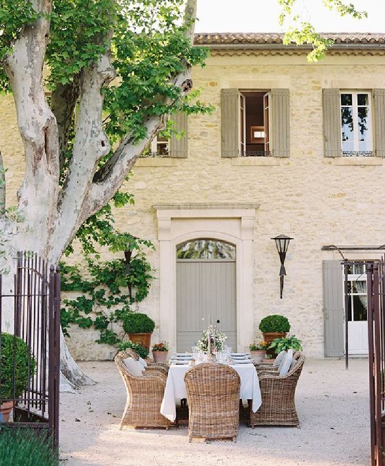 Pale stone French manor house with grey shutters and doors and dining on the gravel motor court. #frenchhome #countryhouse #southoffrance #provence #outdoordining
