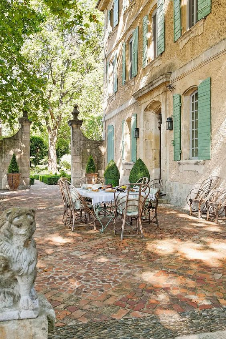 Cheerful green shutters on warm sunny-hued stucco Chateau Mireille in Provence. #frenchchateau #frenchhome #houseexterior #shutters #outdoordining #southoffrance #vacationvilla #provence