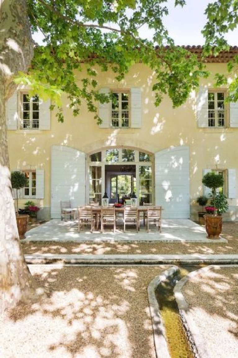 Provence style and charm reign in this picturesque outdoor dining patio with topiaries bathed in dappled light. #provence #french #chateau #outdoordining
