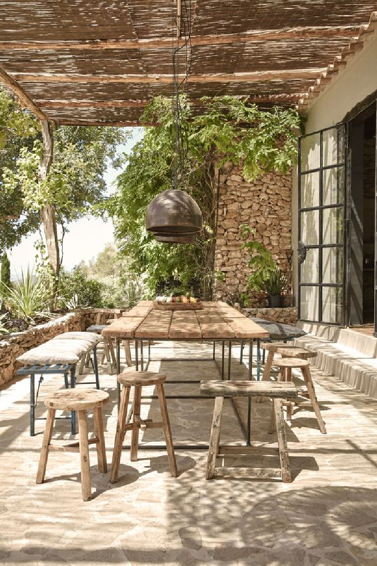 Rustic wood benches and stools at farm table on a Tuscan patio. #tuscanstyle #rustic #outdoordining #farmhouse #italianrustic