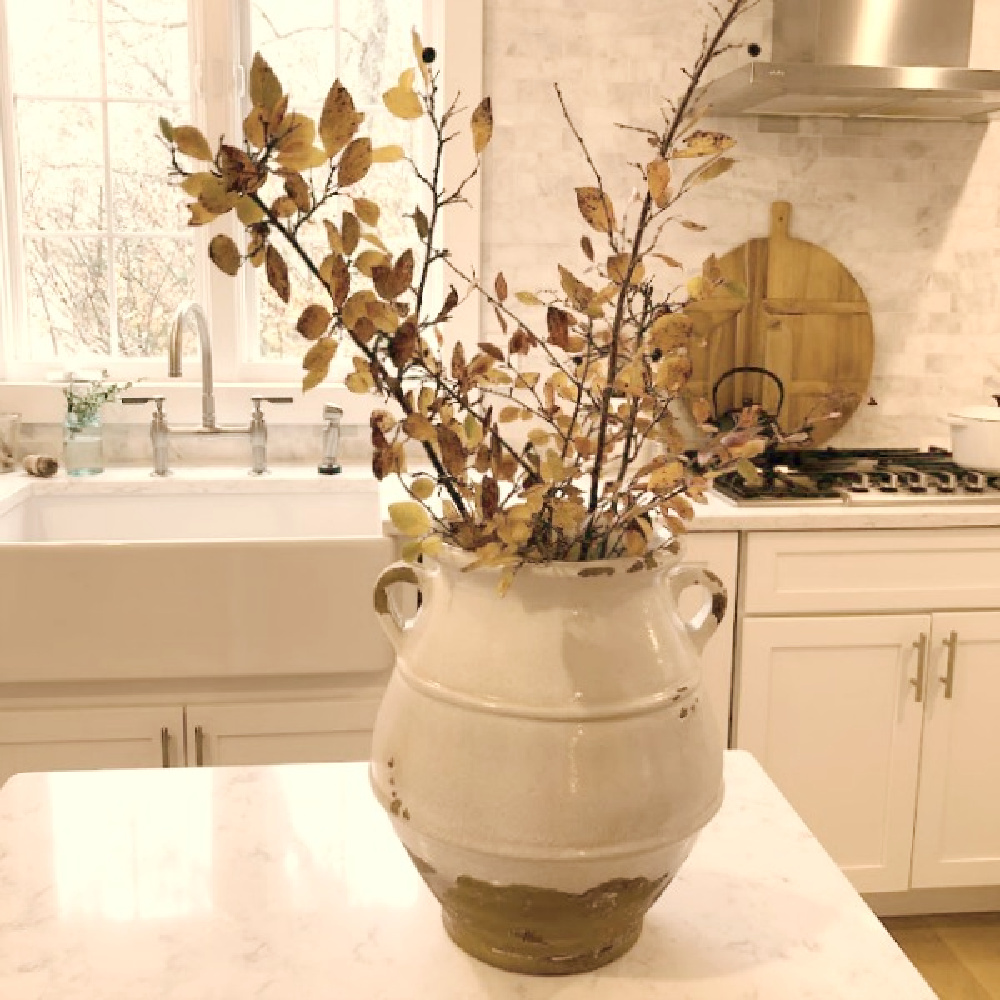Terracotta urn with fall branches on the work table in my white European country modern French kitchen - Hello Lovely.