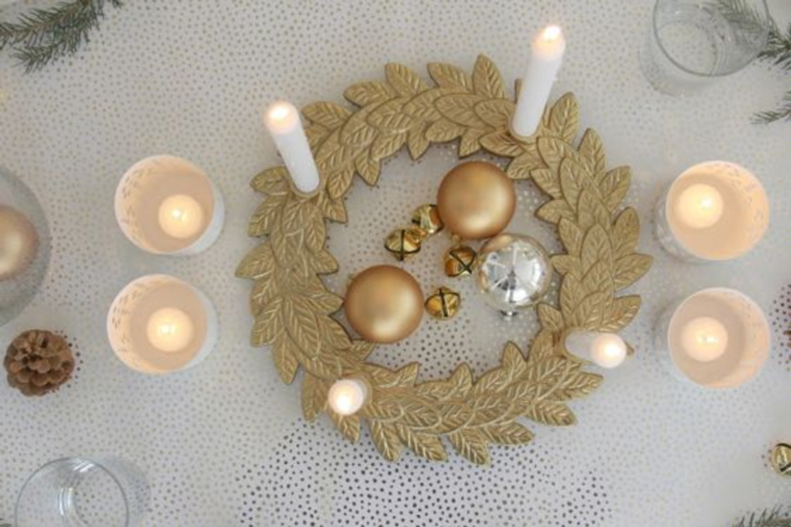 Gold and white Christmas table with advent wreath, gold ornaments, and candlelight - Hello Lovely Studio. #adventwreath #goldchristmas #goldandwhite #christmasdecor #christmastable