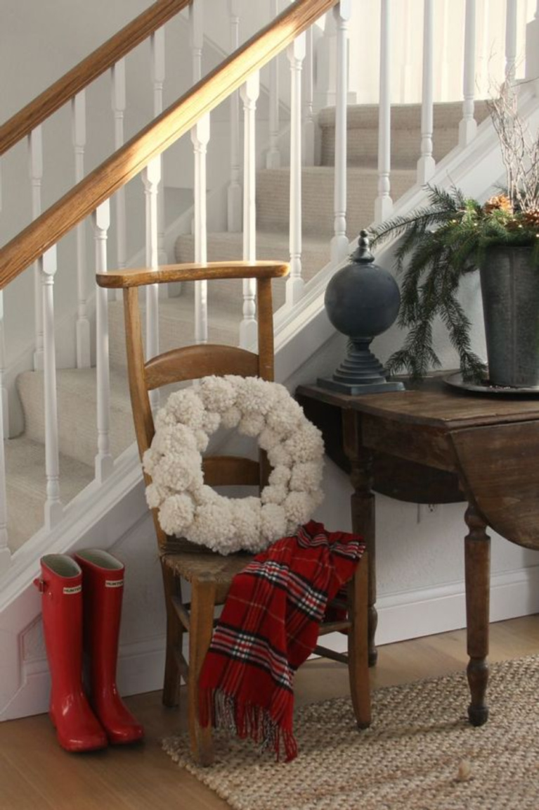 Christmas decor in Hello Lovely's entry is as simple as red boots, plaid scarf, and pom pom wreath. #hellolovelystudio #christmasdecor #holidaydecorating #simplechristmas #pompomwreath #redboots #holidayhomes and