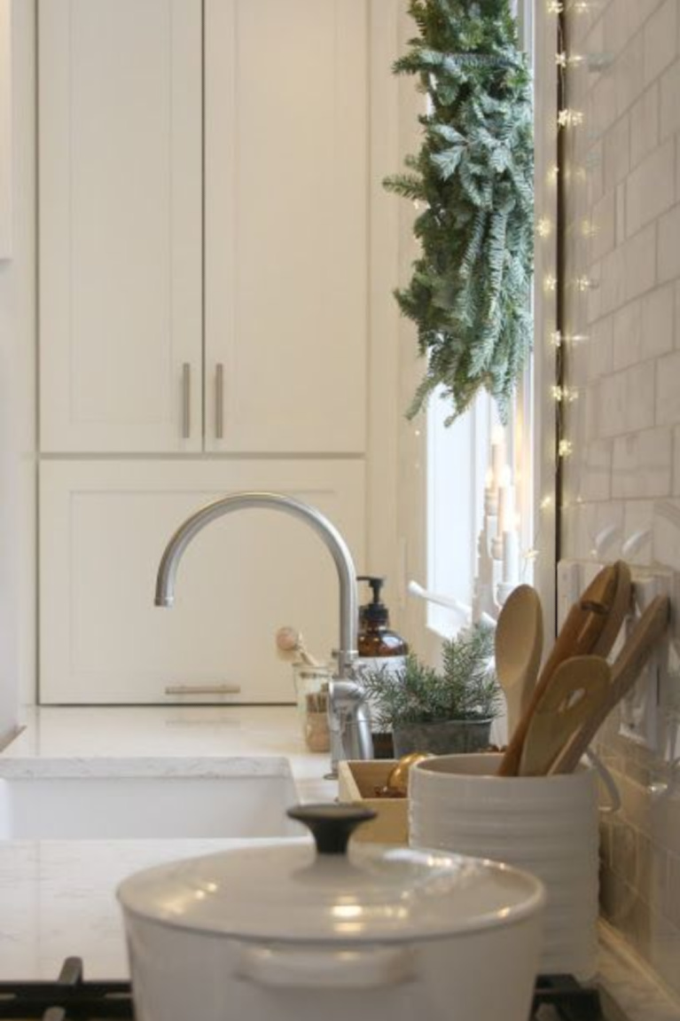 White Scandi inspired Christmas kitchen with fairy lights, fresh green wreath on window, and white decor - Hello Lovely Studio. #christmasdecor #whitechristmas #christmaskitchen #scandichristmas #serenechristmas #modernfarmhouse