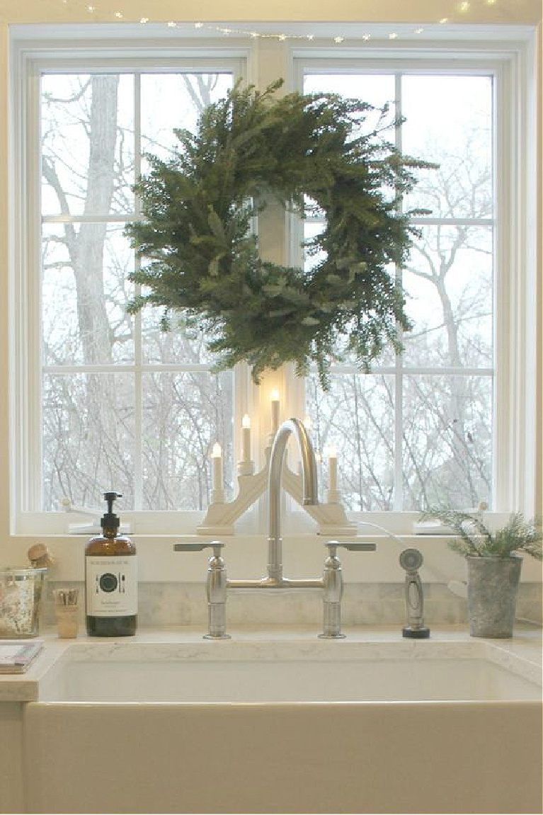 White Scandi Christmas decor in my farmhouse kitchen with Frasier fir wreath and Swedish candelabra at the farm sink in our white kitchen - Hello Lovely Studio. #christmasdecor #christmaswreath #hellolovelystudio #scandichristmas #christmaswreaths #candelabra #swedishchristmas