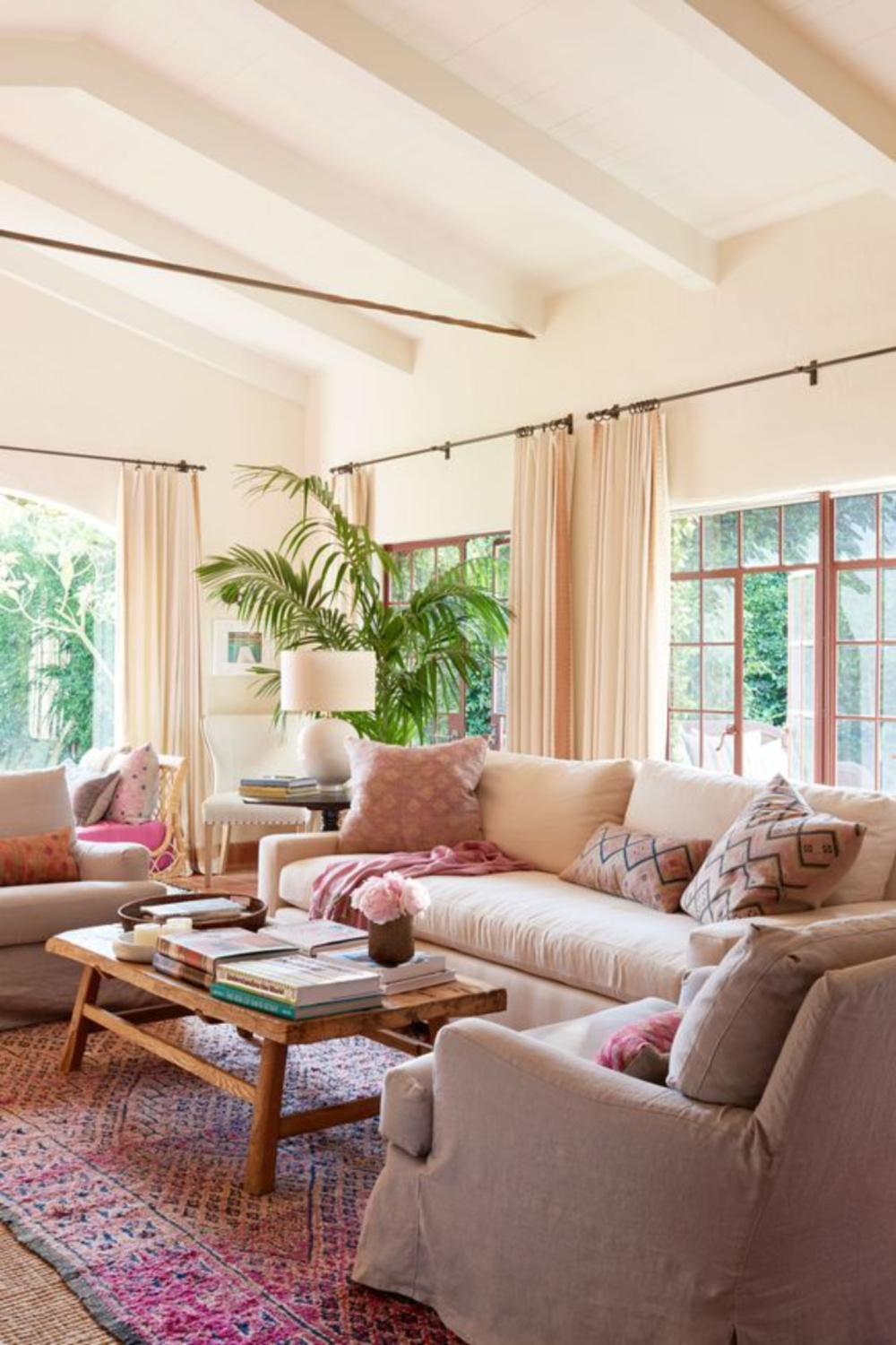 """Reese Witherspoon's House in """"Home Again"""" Movie. A pretty living room with California happy chic, linen furniture, and pops of pink. It's actually the living room in the Spanish hacienda of Reese Witherspoon's House in HOME AGAIN. #livingroom #california #reesewitherspoon #homeagain"""